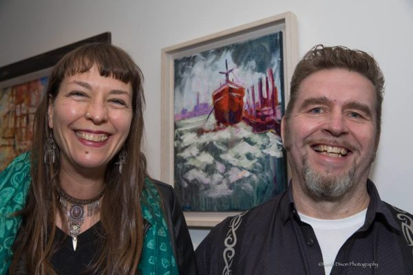 """Anja & Rod Coyne grinning in front of Rod's """"Red Hull"""" painting at the official (pardon the pun) launch. Photo by Keith Dixon."""