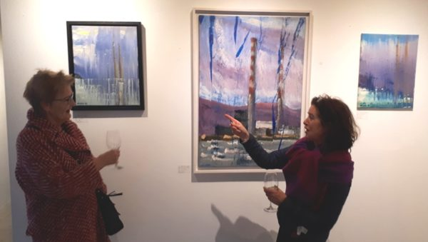 """Coyne's """"Pigeon House"""" collection kept visitors rapt with his contemporary take on Dublin Bay's icon skyline. Two Dublin Docklands visitors in animated discussion before three canvases from this singular collection."""