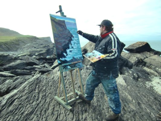 Perched on the edge of the world, Rod Coyne paints on Valentia Island, Co. Kerry.