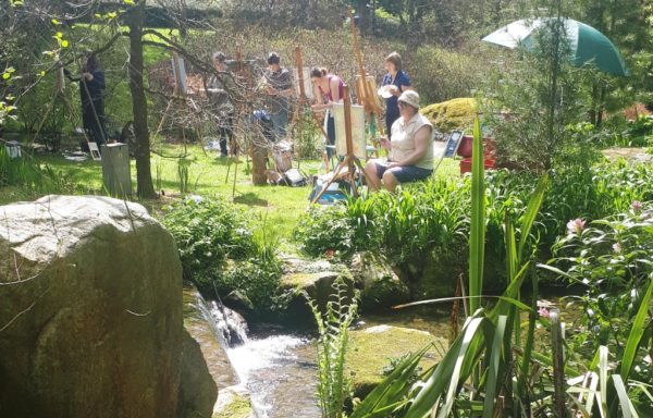 A Photo of students painting in the sunshine beside a tranquil stream in Knocanree Gardens, Avoca.
