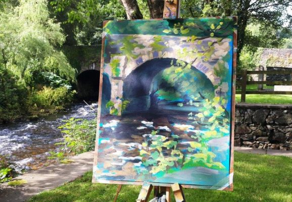 Photo of Rod Coyne's demo piece from the June Painting Workshop in 2019. It depicts a painting of the bridge on the easel with the stone bridge in the background.