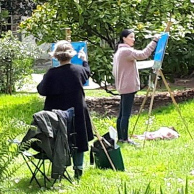 Photo of students enjoy working in the sunshine at the July Painting Workshop from 2019.