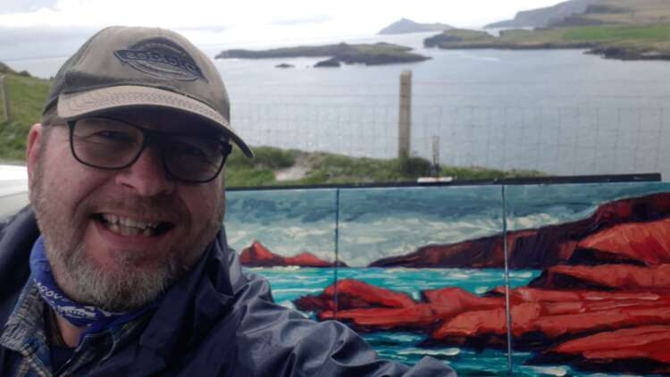 photo of rod coyne, just finished his painting of puffin sound, the painting is on the easel behind him and puffin sound is just behind that.
