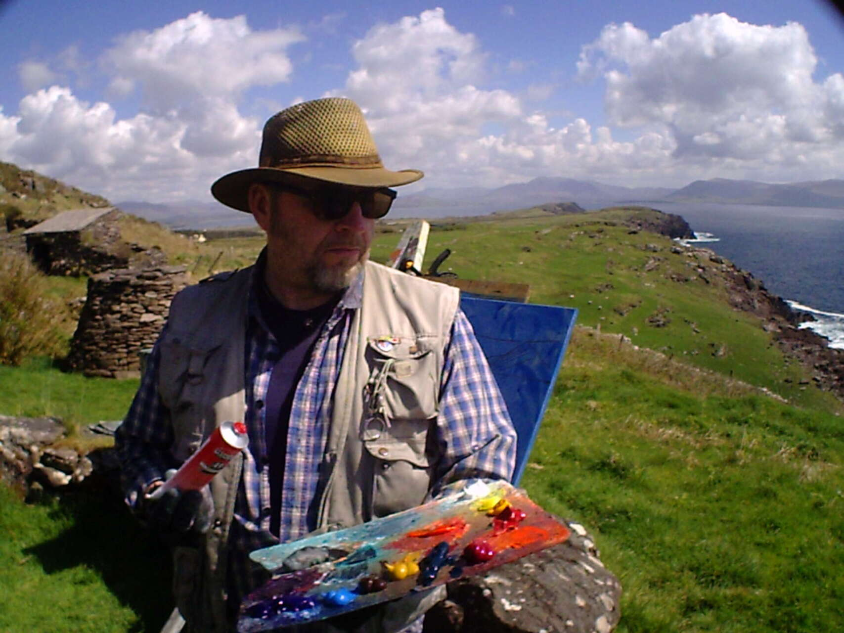 artist rod coyne squeezes extra red paint onto his palette, while working on a clifftop above ballinskelligs bay